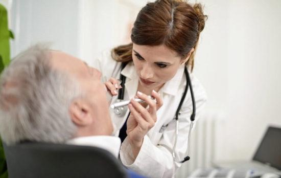 Доктор осматривает горло пациента